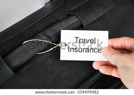 Close-up Of Hand Holding Travel Insurance Tag Tied To A Suitcase - stock photo