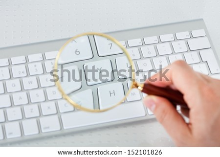 Close-up of hand looking at keyboard key through magnifying glass - stock photo