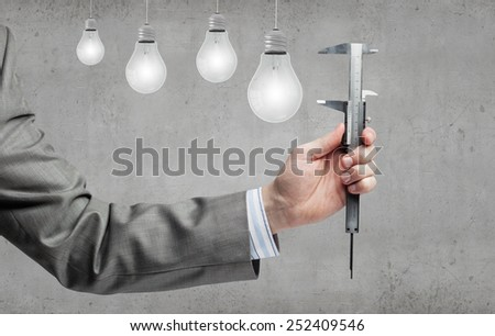 Close up of hand measuring light bulb with wrench - stock photo