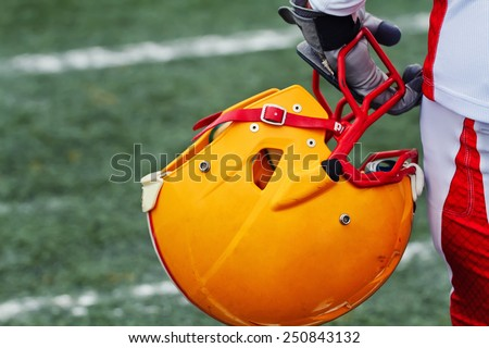 Close up of hand of american football player with yellow helmet on stadium grass background - stock photo