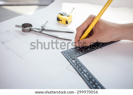 Close up of hand of engineer blueprinting the plan of new building with a ruler and pencil. There are a compass and tape-measure on the table - stock photo
