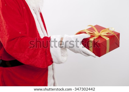 Close up of hand of Santa Claus. He is holding a red box of gift on his palm.