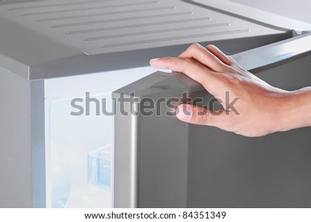 close up of hand opening refrigerator - stock photo