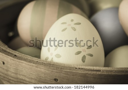 Close up of hand painted Easter eggs piled in a wicker basket.  Striped and plain varieties in background with pale yellow and green floral egg in foreground.  Vintage or retro style. - stock photo