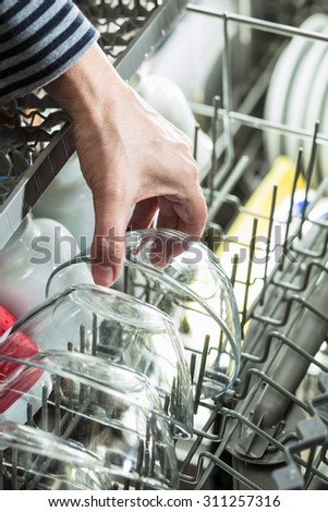 Close up of hand picking clean dishes from dish washer