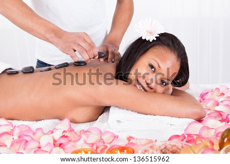 Close-up Of Hand Placing Lastone On Woman Back - stock photo