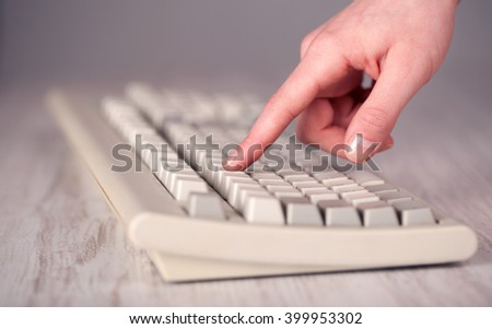 Close up of hand pressing keyboard buttons on desk - stock photo
