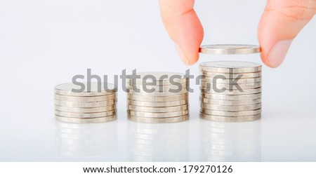 Close up of hand put coins to Stack Of Coins - stock photo