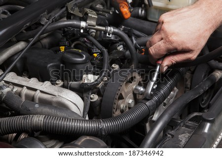 Close-up Of Hand Repairing Car Engine - stock photo