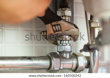 Close up of hand repairing pipes with wrench - stock photo