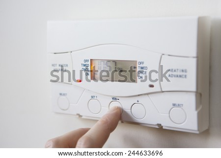 Close Up Of Hand  Setting Control For Heating And Hot Water - stock photo