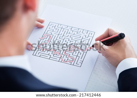Close-up Of Hand Solving Maze Puzzle With Red Pen - stock photo