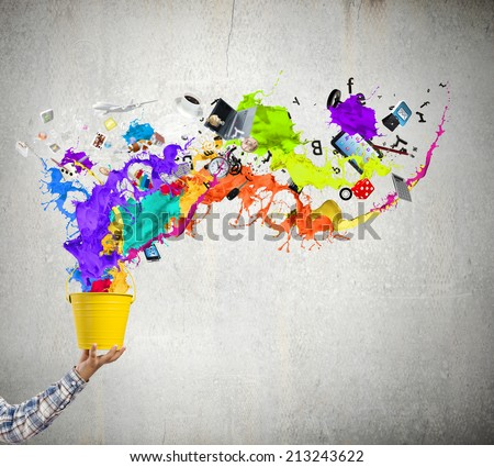 Close up of hand splashing colorful paint from bucket - stock photo