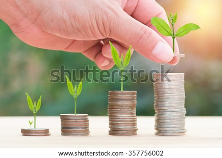 Close up of hand stacking gold coins with green bokeh background ,Business Finance and Money concept,Save money for prepare in the future.Trees growing on coin - stock photo