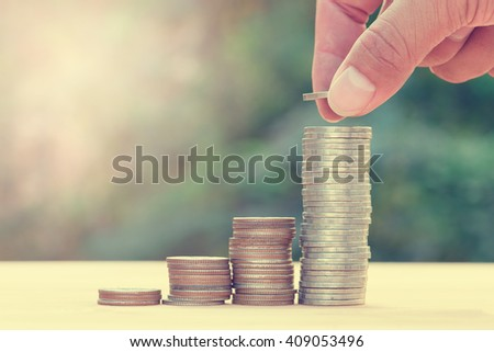 Close up of hand stacking gold coins with green bokeh background ,Business Finance and Money concept,Save money for prepare in the future. - stock photo