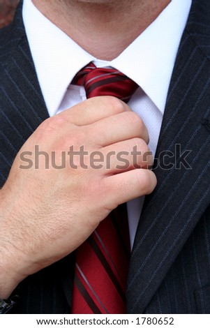 Close up of hand straighting red tie