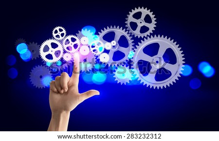 Close up of hand touching icon of gears on media screen