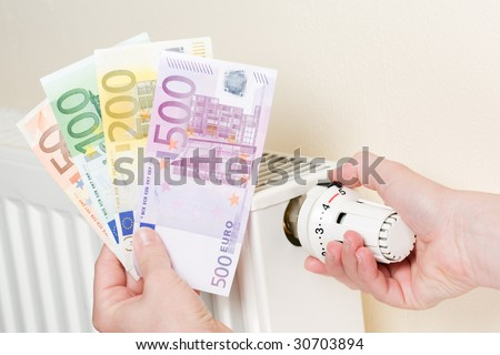 Close-up of hand turning thermostat to zero heating position expressing energy and cost waste - stock photo