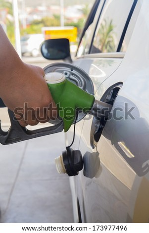 close up of hand with pump refilling car with fuel
