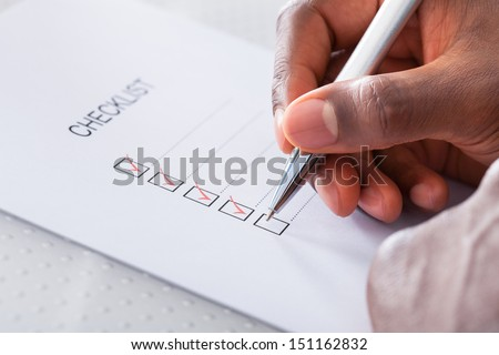 Close-up Of Hand With Red Pen Marking A Check Box - stock photo