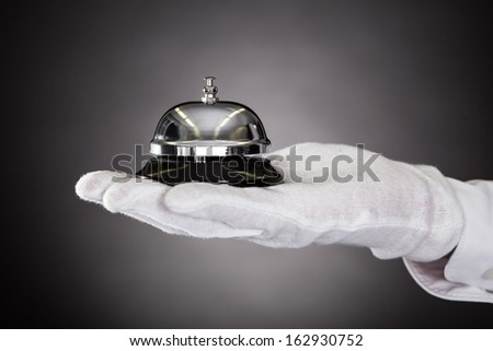 Close-up Of Hand With White Gloves Holding Service Bell - stock photo