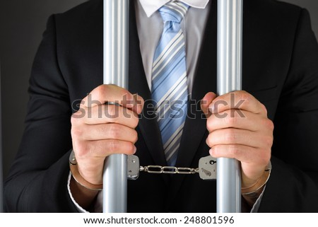 Close-up Of Handcuffed Businessman In Jail Holding Metal Bars - stock photo