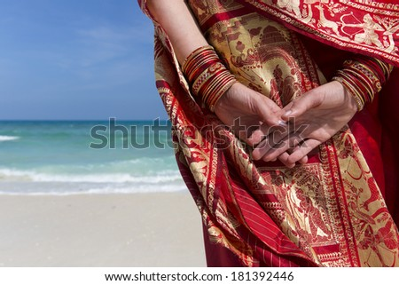 Close up of hands and bangles of a woman wearing a saree looking out to sea. - stock photo