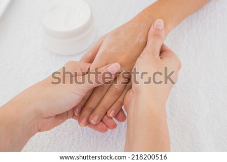Close up of hands applying cream over table - stock photo