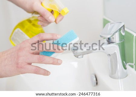 Close Up Of Hands Cleaning Bathroom Sink - stock photo
