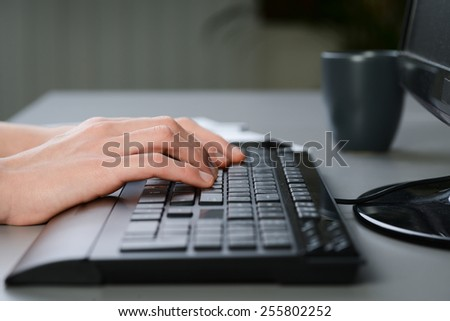 close up of hands detail typing on a desktop computer keyboard - stock photo