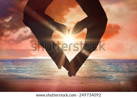 Close up of hands forming heart against sunrise over magical sea - stock photo