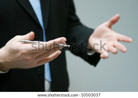 close up of hands gesturing while holding pen and torso of man with business suit and blue tie - stock photo