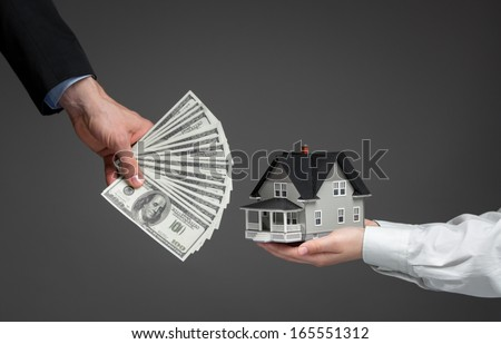 Close up of hands giving house model to other hands with money. Concept of real estate and deal - stock photo