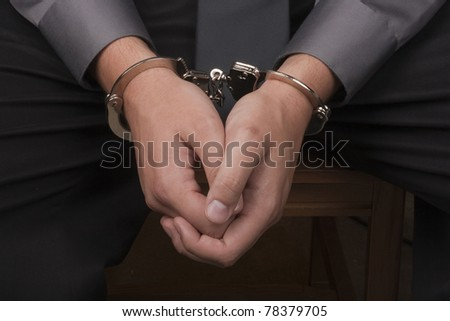 Close-up of hands handcuffed, arrested for questioning. - stock photo