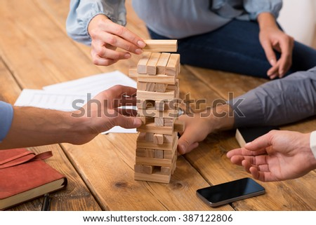 Close up of hands helping build a building of wooden pieces. Businesspeople planning a new business strategy. Business team trying to generate new ideas with wooden bricks. Business risk concept.  - stock photo