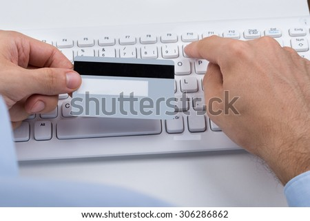 Close-up Of Hands Holding Credit Card On A Computer Keyboard - stock photo