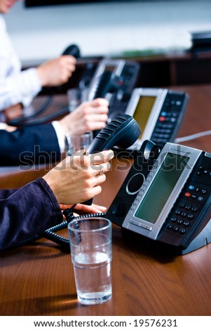 Close-up of hands holding landline phone recievers at customer service office. - stock photo