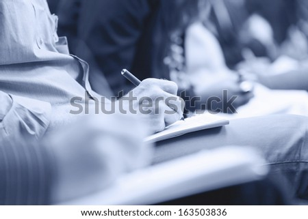 Close-up of Hands holding pens and making notes at the conference. Monochromatic