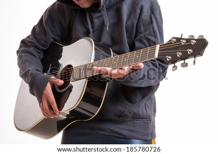 Close up of hands learning to playing an acoustic guitar - stock photo