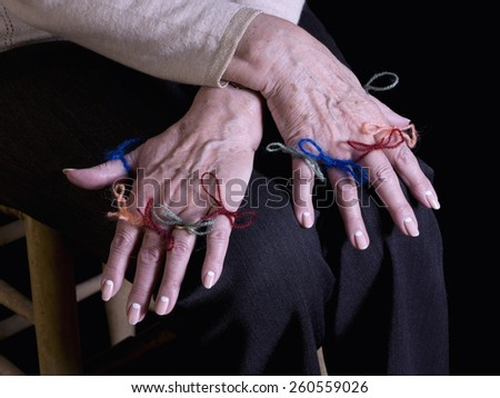 Close up of hands of an old woman, with strings attached in the fingers, remembering something - stock photo