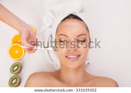 Close up of hands of beautician applying clay cosmetic mask on female face. The woman is lying and smiling at spa. She closed eyes with pleasure - stock photo