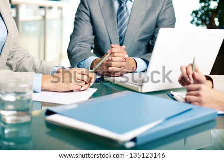 Close-up of hands of boss at workplace with laptop and hands of two females near by - stock photo