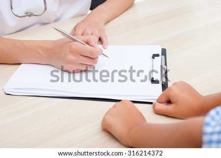 Close up of hands of female pediatrician seeing her patient. The woman and boy are sitting at the table. She is writing down some data with concentration - stock photo