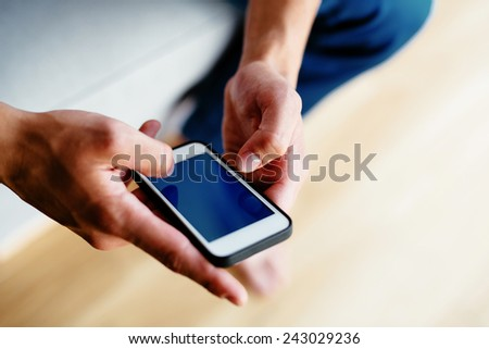 Close-up of hands of man using smartphone - stock photo