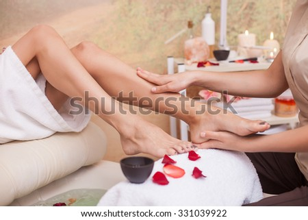 Close up of hands of masseuse massaging female legs at spa. The woman is sitting near small bath with petals - stock photo