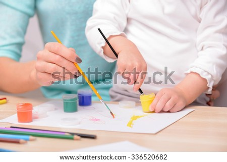Close up of hands of mother and daughter painting together. They are sitting at the desk - stock photo