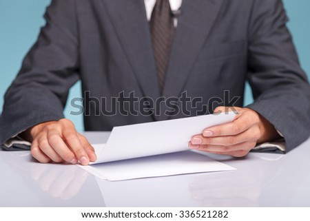 Close up of hands of young anchorman in suit sitting at table in studio. The man is holding documents