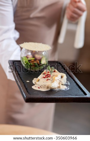 Close up of hands of young cafe worker holding a tray of food. The man is standing and carrying a towel - stock photo