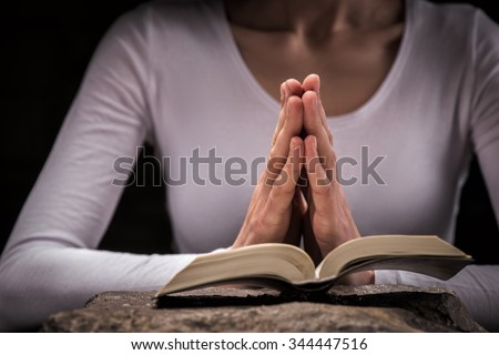 Close up of hands of young girl praying near the Bible. She is sitting near the stone surface and clasping her arms together - stock photo