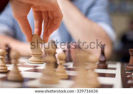 Close up of hands of young man and woman playing chess. They are sitting opposite each other - stock photo